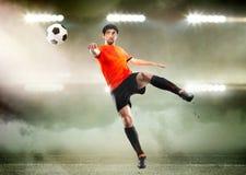 Футболист поражая шарик на стадионе Стоковая Фотография RF