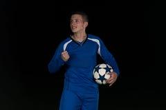 Футболист празднуя победу на черной предпосылке Стоковая Фотография RF