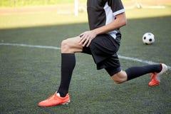 Футболист протягивая ногу на футболе поля стоковое изображение rf