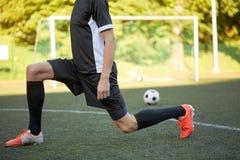 Футболист протягивая ногу на футболе поля стоковое изображение
