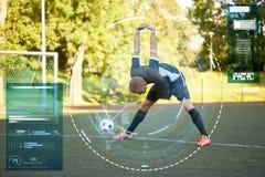 Футболист протягивая ногу на футболе поля стоковое фото rf