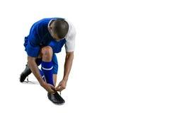Футболист связывая его шнурок ботинка стоковая фотография
