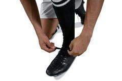 Футболист связывая его шнурок ботинка стоковое изображение