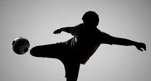 Футболист силуэта пиная шарик Стоковые Фотографии RF