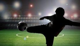 Футболист силуэта пиная шарик стоковое фото rf