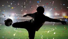 Футболист силуэта пиная шарик стоковая фотография rf