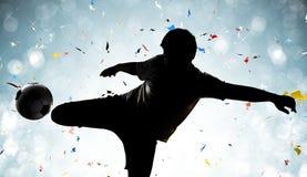 Футболист силуэта пиная шарик Стоковое Изображение