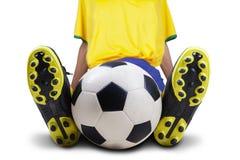 Футболист сидя при изолированный шарик стоковое изображение