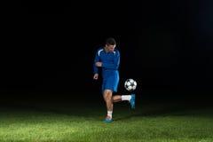 Футболист с шариком на поле стадиона Стоковое Изображение
