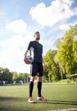 Футболист с шариком на футбольном поле стоковая фотография