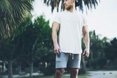 Футболка бородатого мышечного человека фото нося белая пустая в временени зеленый цвет сада города Расслабляющее время после труд Стоковое фото RF