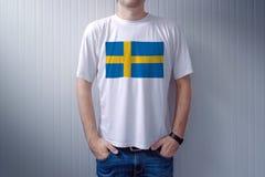 Футболка красивого вскользь человека нося белая с шведским языком сигнализирует Стоковые Изображения RF