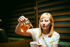 Футболка молодой белокурой женщины нося белая при печать, сидя на таблице в кафе Стоковые Изображения