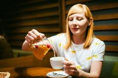 Футболка молодой белокурой женщины нося белая при печать, сидя на таблице в кафе Стоковая Фотография RF
