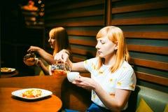 Футболка молодой белокурой женщины нося белая при печать, сидя на таблице в кафе Стоковые Фото