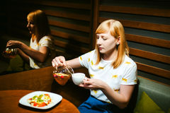 Футболка молодой белокурой женщины нося белая при печать, сидя на таблице в кафе Стоковая Фотография