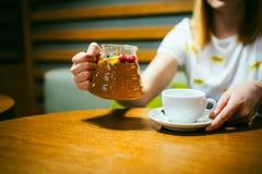 Футболка молодой белокурой женщины нося белая при печать, сидя на таблице в кафе Стоковое фото RF