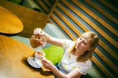 Футболка молодой белокурой женщины нося белая при печать, сидя на таблице в кафе Стоковые Фотографии RF