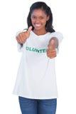 Футболка молодой женщины нося добровольные и давать большие пальцы руки вверх стоковое фото rf