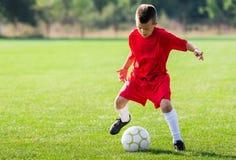 футбол мальчика шарика пиная стоковые изображения
