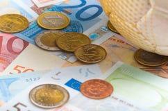 Футбол сидя на счетах и монетках денег евро распространения вне, держа пари концепция Стоковая Фотография RF