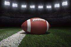 Футбол стиля коллежа на поле с нашивкой под стадионом освещает Стоковые Изображения RF