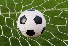 Футбол футбола в сети цели с полем зеленой травы Стоковое фото RF