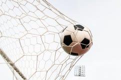 Футбол футбола в сети цели с полем неба Стоковая Фотография RF