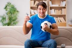 Футбол человека наблюдая дома сидя в кресле Стоковое Изображение