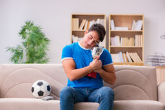 Футбол человека наблюдая дома сидя в кресле Стоковая Фотография RF