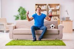 Футбол человека наблюдая дома сидя в кресле Стоковые Изображения RF