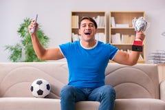 Футбол человека наблюдая дома сидя в кресле Стоковое фото RF