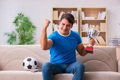 Футбол человека наблюдая дома сидя в кресле Стоковые Фото