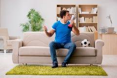 Футбол человека наблюдая дома Стоковое Изображение