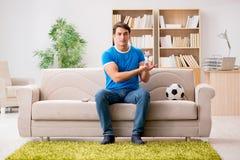 Футбол человека наблюдая дома Стоковые Фото