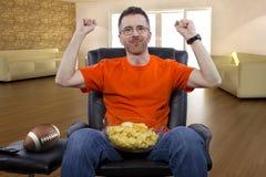 Футбол человека сидя и наблюдая дома Стоковые Изображения RF