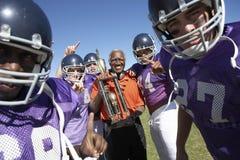 Футбольная команда и тренер с трофеем празднуя победу на поле Стоковое Изображение RF