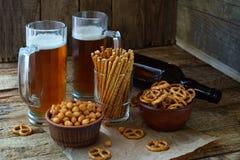 Футбольный болельщик установил с кружками пива, бутылки и солёных закусок на деревянной предпосылке Шутихи, крендель, посоленные  Стоковая Фотография