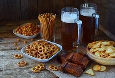 Футбольный болельщик установил с кружками пива и солёных закусок на деревянной предпосылке Шутихи, крендель, посоленные соломы, г Стоковые Фото