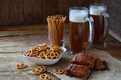 Футбольный болельщик установил с кружками пива и солёных закусок на деревянной предпосылке Шутихи, крендель, посоленные соломы, г Стоковые Изображения