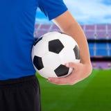 Футбольный мяч в руке игрока на поле большого стадиона Стоковое фото RF