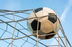 Футбольный мяч в сети цели с предпосылкой голубого неба Стоковое Изображение