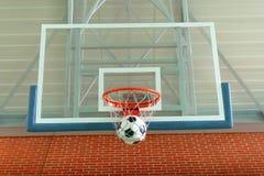 Футбольный мяч пропуская через обруч баскетбола Стоковая Фотография