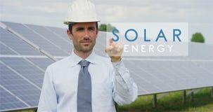 Футуристический технический специалист в солнечных фотовольтайческих панелях, выбирает функцию ` солнечной энергии ` используя чи Стоковые Изображения RF