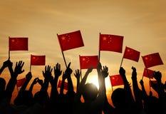 Флаги китайца группы людей развевая в заднем Lit стоковое изображение rf