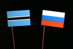 Флаг Ботсваны при русский флаг изолированный на черноте Стоковое Изображение