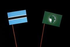 Флаг Ботсваны при флаг Африканского Союза изолированный на черноте Стоковое Изображение