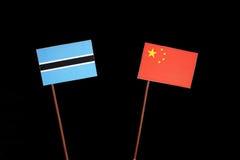 Флаг Ботсваны с китайцем сигнализирует изолированный на черноте Стоковая Фотография RF
