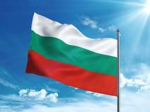 Флаг Болгарии развевая в голубом небе Стоковое Изображение