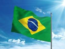 Флаг Бразилии развевая в голубом небе Стоковая Фотография